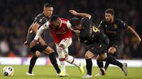 Striker Arsenal, Alexandre Lacazette berusaha melewati tiga pemain Vitoria de Guimaraes pada pertandingan lanjutan Grup F Liga Europa di Stadion Emirates, London (24/10/2019). Arsenal menang tipis atas Vitoria dengan skor 3-2. (AP Photo/Alastair Grant)