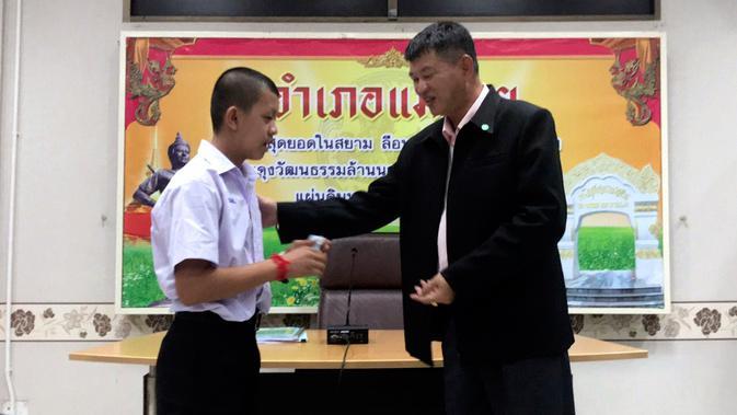 Salah seorang remaja, Pornchai Kamluang menerima kartu identitas sebagai warga negara Thailand di distrik Mae Sai, Rabu (8/8). Korban gua Thailand tersebut selama ini hidup tanpa memiliki status kewarganegaraan (Chiang Rai Public Relations Office via AP)