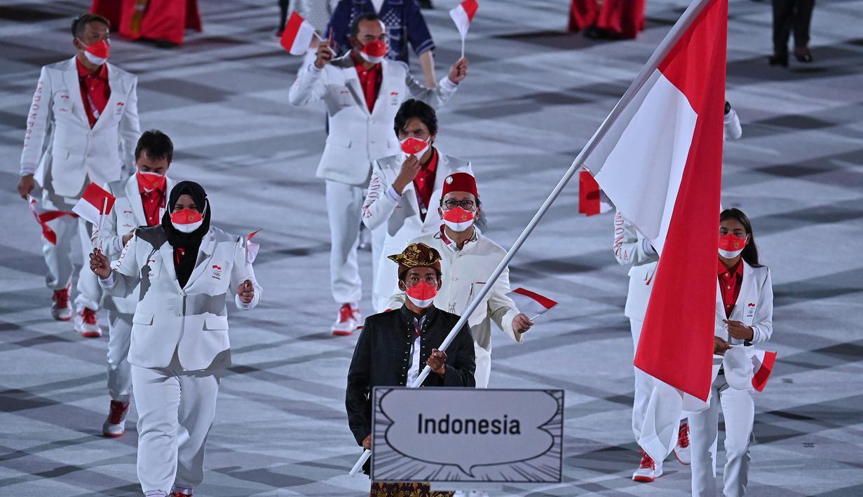 Kontingen Indonesia mengikuti defile dalam pembukaan Olimpiade Tokyo 2020, di Stadion Nasional Jepang, Tokyo, Jumat malam (23/7/2021). Upacara pembukaan Olimpiade Tokyo yang berlangsung dalam era pandemi, dan digelar tanpa penonton. (Ben STANSALL/AFP)