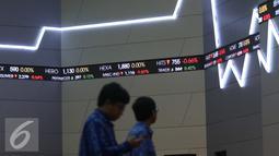 Pengunjung melintasi layar di Bursa Efek Indonesia, Jakarta, Senin (27/6). Pada pembukaan, IHSG masih tertekan dan turun 33,90 poin atau 0,70 persen ke angka 4.800,92. (Liputan6.com/Angga Yuniar)