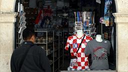 """Gambar pada 28 Maret 2019 menunjukkan seorang turis memasuki toko suvenir """"Game of Thrones"""" di Kroasia. Dubrovnik kini semakin dikenal wisatawan setelah menjadi latar belakang film serial Game of Thrones sejak 2011 untuk jejaring televisi HBO. (Denis LOVROVIC / AFP)"""