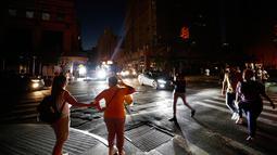 Pejalan kaki menyeberang jalan yang gelap saat terjadi pemadaman listrik di New York, AS, Sabtu (13/7/2019). Tidak ada keterangan mengenai pemadaman listrik yang terjadi di New York. (AP Photo/Michael Owens)
