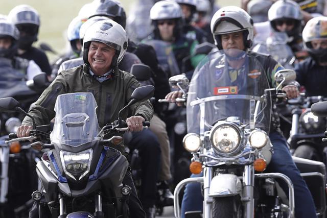 Presiden Brasil Jair Bolsonaro (kiri) melakukan tur sepeda motor dengan para pendukung di Brasilia, di tengah pandemi virus corona pada Minggu (9/5/2021). Bolsonaro memimpin ratusan pengendara motor melakukan perjalanan mengelilingi ibu kota Brasil untuk memperingati Hari Ibu (AP Photo/Eraldo Peres)