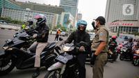 Petugas Satpol PP mengimbau pengguna kendaraan saat melakukan Pengawasan Pelaksanaan PSBB di kawasan Bundaran HI, Jakarta, Senin (13/4/2020). Petugas juga mengimbau mengatur posisi duduk dan pembatasan penumpang untuk kendaraan bermobil baik pribadi maupun angkutan umum. (Liputan6.com/Faizal Fanani)