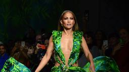 Bintang pop dan aktris Jennifer Lopez menutup peragaan busana Versace untuk Spring/Summer Collection 2020 pada Milan Fashion Week 2019, Jumat (20/9/2019). Jennifer Lopez mengenakan versi baru gaun hijau ikonis yang pernah ia gunakan di Grammy Awards 20 tahun lalu. (Miguel MEDINA/AFP)