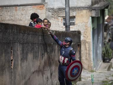 Petugas polisi militer Everaldo Pinto, berkostum superhero Captain America, menyapa anak-anak di tengah pandemi COVID-19 di Petropolis, Rio de Janeiro, Brasil, Kamis (15/4/2021). Pinto memberitahu anak-anak tentang perlunya melindungi diri dari virus corona. (AP Photo/Silvia Izquierdo)