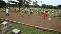 Anak-anak bermain bola di sekitar TPU Karet Bivak, Jakarta, Jumat (13/1). Semakin berkurangnya lahan hijau menyebabkan anak-anak di Ibukota terpaksa bermain di tempat yang tidak semestinya. (Liputan6.com/Immanuel Antonius)