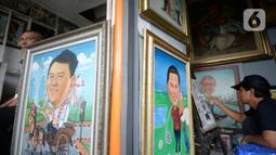 Seorang pelukis sedang menyelesaikan lukisan tokoh-tokoh nasional di Depan Pasar Baru, Jakarta, Kamis (24/12/2020). Para pelukis memasarkan lukisannnya dengan harga bervariasi dari dari Rp 500 ribu hingga Rp 2,5 juta. (merdeka.com/Dwi Narwoko)