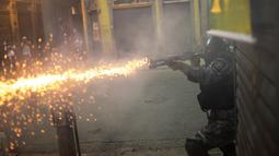 Seorang polisi menembakan gas air mata saat terjadi bentrok di Rio de Janeiro, Brasil, (29/4). Mereka menentang usulan perubahan undang-undang ketenagakerjaan dan sistem pensiun. (AP Photo/Leo Correa)