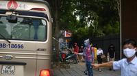 Petugas kesehatan menyemprotkan desinfektan pada bus sekolah di sekolah Marie Curie di Hanoi, Senin (4/5/2020). Vietnam membuka kembali aktivitas sekolah yang ditutup selama tiga bulan setelah dilaporkan tidak ada kasus virus corona COVID-19 baru hingga Sabtu, 2 Mei 2020. (Manan VATSYAYANA/AFP)