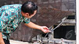 Petugas BNN mengecek kondisi tembok ruang tahanan yang dijebol para tahanan untuk melarikan diri, Jakarta, Selasa (31/3/2015). Tembok ruang tahanan BNN berukuran 16 milimeter, luas jebolan 30 sentimeter (cm) dengan lebar 40 cm. (Liputan6.com/Yoppy Renato)