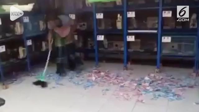 Sebuah video menunjukkan seorang pria yang menyapu uang yang berserakkan. Video ini menjadi viral dan dibicarakan warganet.