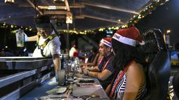 Pelayan melayani pengunjung restoran gantung dengan dekorasi kereta salju santa claus di Kuala Lumpur, Malaysia, Rabu (5/12). Pengunjung ditawarkan sensasi bepergian dengan kereta salju santa claus lengkap dengan rusa. (MOHD RASFAN/AFP)