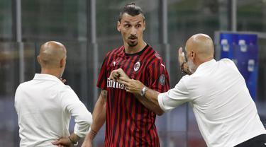 Pelatih AC Milan, Stefano Pioli, berusaha menenangkan Zlatan Ibrahimovic yang kecewa usai diganti saat melawan Bologna pada laga Serie A di Stadion San Siro, Sabtu (18/7/2020). AC Milan menang dengan 5-1 atas Bologna. (AP/Luca Bruno)