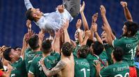 Para pemain Timnas Meksiko mengangkat sang pelatih, Jaime Lozano, berselebrasi setelah mengalahkan Jepang pada perebutan medali perunggu di sepak bola Olimpiade Tokyo, Kamis (6/8/2021). (AP Photo/Martin Mejia)