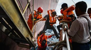 Anggota Basarnas mengevakuasi seorang anak buah kapal (ABK) dari kapal tanker asing berbendera Bahama di lepas pantai Aceh, Selasa (30/7/2019). Basarnas mendapat permintaan pertolongan setelah seorang ABK kapal tanker mengalami sakit jantung di perairan Aceh. (CHAIDEER MAHYUDDIN/AFP)