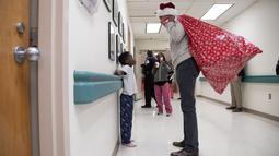 Mantan Presiden AS, Barack Obama mengobrol dengan seorang pasien anak di Children's National Medical Center , Washington, Rabu (19/12). Obama mengunjungi anak-anak yang sedang menjalani perawatan di sana untuk membagikan kado Natal. (Chuck Kennedy / AFP)