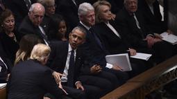 Presiden AS Donald Trump menyapa mantan presiden Barack Obama dan Michele Obama saat menghadiri prosesi pemakaman kenegaraan Presiden AS ke-41, George HW Bush di Katedral Nasional Washington, Rabu (5/12). (Brendan SMIALOWSKI/AFP)