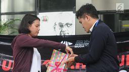 Presiden BEM KM UGM Obed Kresna Widyapratistha (kanan) menyerahkan kado kepada perwakilan Biro Humas KPK Brigita Simbolon di Gedung KPK Jakarta, Senin (10/12). Aksi simpatik ini untuk memperingati Hari Anti Korupsi Sedunia. (Merdeka.com/Dwi Narwoko)