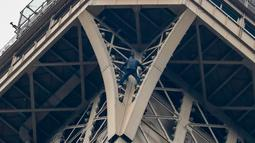 Seorang pria tak dikenal nekat memanjat Menara Eiffel tanpa peralatan keselamatan di Paris, Senin (20/5/2019). Tim pemadam kebakaran termasuk seorang spesialis pendakian berada di lokasi dan menghadapi penyusup itu yang motivasinya masih belum diketahui. (FRANCOIS GUILLOT / AFP)