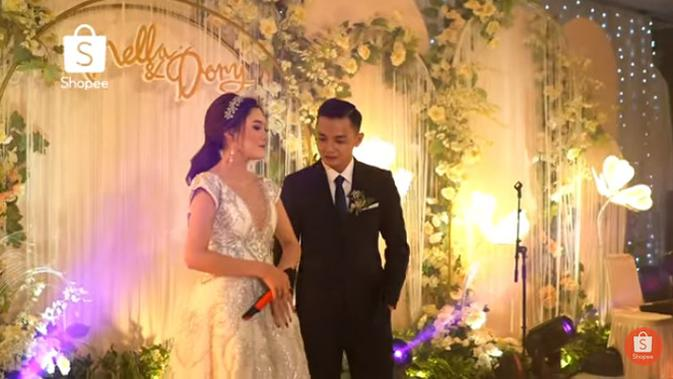 Syahrini sebagai pembawa acara tersebut meminta pasangan penyanyi itu membuktikan kebenaran kalau sudah menikah. Nella dan Dory memperlihatkan cincin yang ada di jari manis masing-masing. (Youtube/SHOPEE Indonesia)