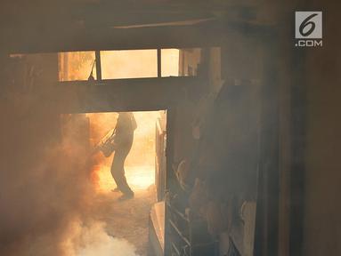Petugas melakukan fogging nyamuk demam berdarah dengue (DBD) di salah satu rumah warga RW 01, Kelurahan Cipinang, Jakarta, Minggu (10/3). Fogging dilakukan setelah beberapa warga di permukiman tersebut terkena DBD. (merdeka.com/Iqbal Nugroho)