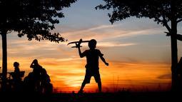 Seorang anak laki-laki bermain dengan pesawat mainan saat matahari terbenam di bukit Kronberg di Hannover, Jerman utara (6/8). (AP Photo/Julian Stratenschulte)