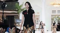 Penampilan Yuki saat berjalan di atas panggung catwalk mengenakan kebaya kutu baru hitam dengan kombinasi celana bermotif. (Liputan6.com/IG/@yukikt)