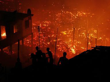 Warga berusaha memadamkan api dengan air saat kebakaran di lingkungan Educandos, di Manaus, Brasil (17/12). Para pihak berwenang mengatakan setidaknya 600 rumah kayu hanggus terbakar. (AP Photo/Edmar Barros)