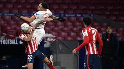 Pemain Atletico Madrid, Mario Hermoso, duel udara dengan pemain Sevilla, Lucas Ocampos, pada laga Liga Spanyol di Stadion Wanda Metropolitano, Selasa (12/1/2021). Atletico Madrid menang dengan skor 2-0. (AFP/Pierre-Philippe Marcou)