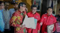Menkumham Yasonna Laoly memperlihatan berkas yang diserahkan Hasto Kristianto di Kantor Kemenkumham, Jakarta, Rabu (6/5/2015). Kedatangan Hasto untuk menyerahkan susunan Kepengurusan DPP PDIP periode 2015-2020 kepada Yasonna. (Liputan6.com/ Faizal Fanani)