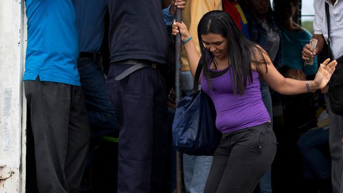 Seorang wanita turun dari truk kargo yang berfungsi sebagai transportasi umum di Villa de Cura, Venezuela, Senin (22/1). Pemilik truk lebih suka membawa penumpang daripada barang dagangan karena penjarahan kian marak. (AP Photo/Fernando Llano)