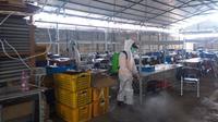 Tim BPBD Purbalingga menyemprot cairan disinfektan di pabrik lokasi penemuan pasien positif COVID-19 di Purbalingga, Minggu (15/11/2020). (Foto: Liputan6.com/Istimewa)