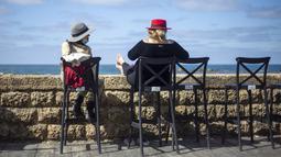 Pengunjung duduk di bar kafe yang menghadap ke Laut Mediterania saat pembatasan dilonggarkan di Tel Aviv, Minggu (7/3/2021). Israel membuka kembali sebagian besar ekonominya sebagai bagian dari fase terakhir pencabutan kebijakan lockdown yang berlaku sejak September lalu. (AP Photo/Ariel Schalit)