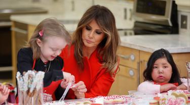 Istri Presiden AS, Melania Trump membantu seorang anak menghias kue saat berkunjung ke Children's Inn di National Institute of Health (14/2). Mengenakan jas merah, Melania bertukar kartu valentine dengan anak-anak. (AP Photo/Pablo Martinez Monsivais)