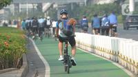 Warga bersepeda di jalan Sudirman, Jakarta, Selasa (1/6/2021). Direktorat Lalu Lintas Polda Metro Jaya tengah mengkaji sanksi sita sepeda apabila menemukan pesepeda yang gowes di luar jalur khusus yang telah disediakan. (merdeka.com/Imam Buhori)