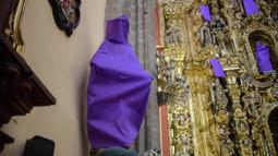 Patung perempuan ditutupi dengan kain ungu di Gereja De los Santos Cosme y Damian di Mexico City, pada Rabu (4/3/2020). Penutupan patung tersebut sebagai bentuk protes terhadap kekerasan gender. (Photo by Pedro PARDO / AFP)