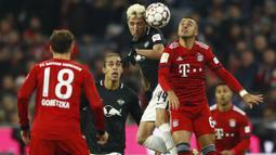 Gelandang Bayern Munich, Thiago, duel udara dengan pemain RB Leipzig, Kevin Kampl, pada laga Bundesliga di Allianz Arena, Kamis (20/12). Bayern Munich menang 1-0 atas RB Leipzig. (AP/Matthias Schrader)