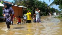 Sejumlah warga menerobos banjir yang merendam Sidareja, Cilacap, Desember 2017. (Foto: Liputan6.com/Muhamad Ridlo)