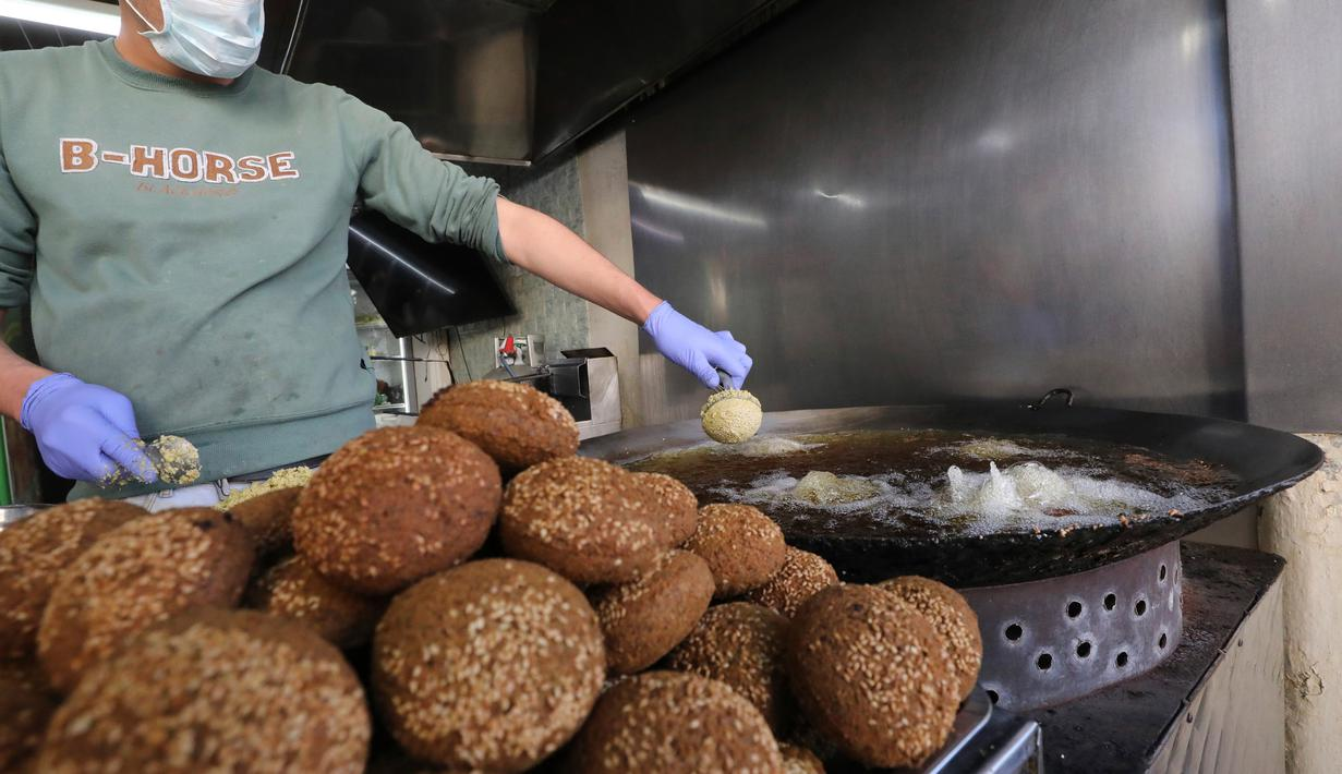 Juru masak Palestina mengenakan sarung tangan dan masker saat menggoreng falafel di sebuah restoran lokal di kota Hebron, Tepi Barat yang diduduki pada 29 April  2020. Pada bulan suci Ramadan, falafel sering dimakan sebagai hidangan buka puasa. (HAZEM BADER / AFP)