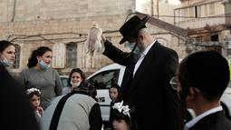 Seorang pria Yahudi ultra-Ortodoks mengayunkan ayam di atas kepala keluarganya sebagai bagian dari ritual Kaparot di Yerusalem, Rabu (23/9/2020). Tradisi itu digelar sebelum perayaan Yom Kippur atau hari Penebusan dosa, hari paling suci dalam tahun Yahudi. (AP Photo/Maya Alleruzzo)
