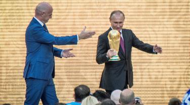 """Presiden Rusia Vladimir Putin memegang trofi Piala Dunia dalam pembukaan upacara  """"FIFA World Cup Trophy Tour"""" di stadion Luzhniki di Moskow (9/9). Piala Dunia 2018 adalah Piala Dunia FIFA ke-21. (AFP Photo/Mladen Antonov)"""