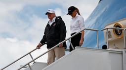 Presiden AS, Donald Trump dan Ibu Negara Melania Trump turun dari pesawat kepresidenan di Bandara Internasional Austin, Texas, Selasa (29/8). Trump mencoba menyemangati warganya lewat kunjungan ke Texas yang dihantam badai Harvey. (AP Photo/Evan Vucci)