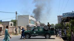 Personel keamanan Afghanistan memblokade jalan dekat ledakan bom bunuh diri di Jalalabad, Selasa (31/7). Pria bersenjata menyerang gedung pemerintahan, membuat puluhan orang terperangkap setelah pelaku meledakkan bom bunuh diri. (AFP/NOORULLAH SHIRZADA)