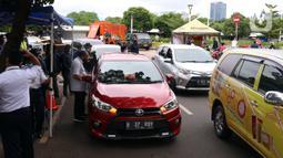Antrean pengendara mobil saat uji emisi gratis di Jakarta Barat, Rabu (13/1/2021). Dinas Lingkungan Hidup DKI Jakarta mengumumkan kendaraan yang tidak mengikuti uji emisi atau tidak lulus uji emisi gas buang akan dikenakan disinsentif tarif parkir yang tinggi dan tilang. (Liputan6.com/Angga Yuniar)
