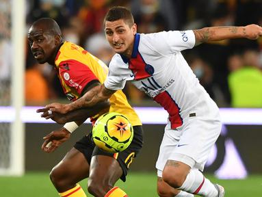 Gelandang PSG, Marco Verratti, berebut bola dengan gelandang Lens, Gael Kakuta, pada laga Liga Prancis di Stadion Bollaert-Delelis, Jumat (11/9/2020). PSG kalah 0-1 atas Lens. (AFP/Denis Charlet)