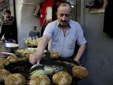 Pedagang membuat kudapan Falafel untuk menu berbuka puasa selama Ramadan di Kota Nablus, Tepi Barat, Minggu (26/4/2020). (AP Photo/Majdi Mohammed)