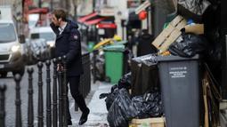Seorang pria berjalan melewati tong sampah di Paris (4/2/2020). Serikat pekerja memutuskan kegiatan di pabrik pembakaran kunci untuk memprotes reformasi yang mereka katakan tidak adil. (AP Photo/Christophe Ena)