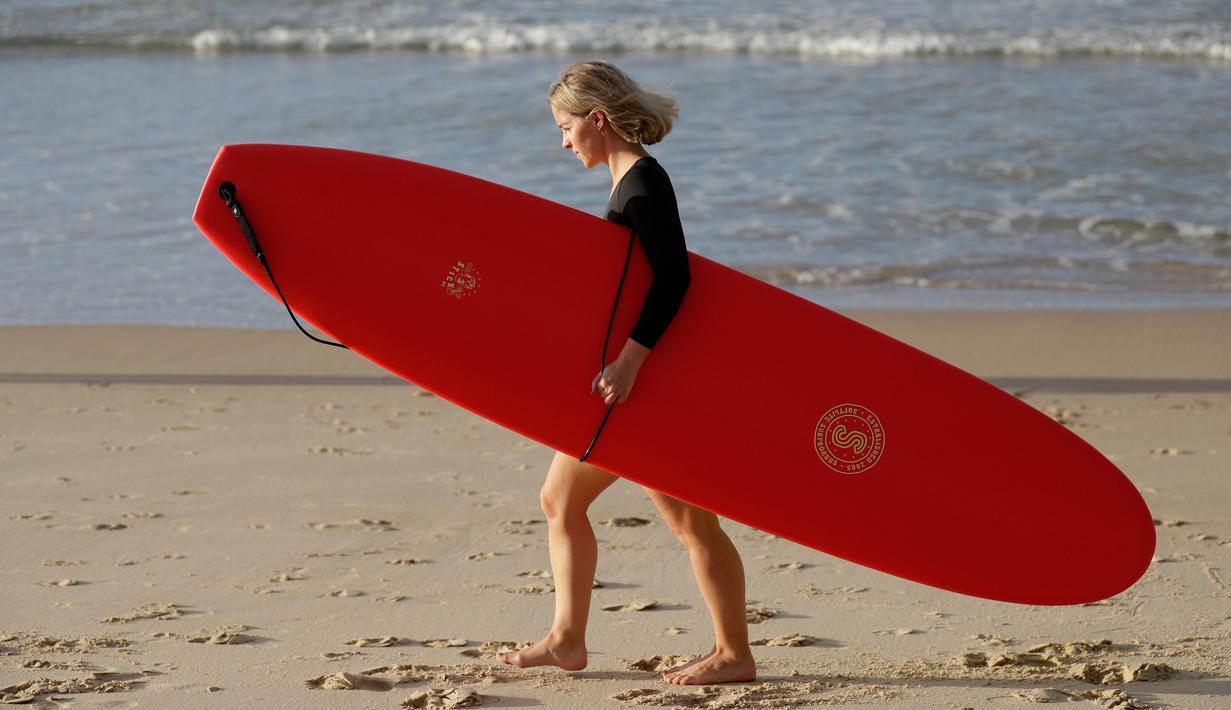 Seorang wanita membawa papan selancar bersiap bermain saat pembatasan sosial Covid-19 mulai dilonggarkan di Pantai Bondi di Sydney, Selasa, (28/4/2020).  Pantai ini terbuka untuk perenang dan peselancar untuk berolahraga saja. (AP Photo/Rick Rycroft)