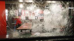 Seorang pria membersihkan dan terlihat melalui kaca yang rusak di sebuah restoran cepat saji yang dihancurkan dalam protes terhadap jam malam di Rotterdam, Belanda, Senin (25/1/2021). Lockdown di Belanda menahan warga untuk keluar rumah. Pelanggar bisa didenda 95 euro. (AP Photo/Peter Dejong)
